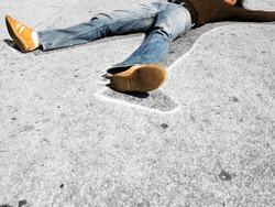 Man lying in dead man chalk outline on concrete