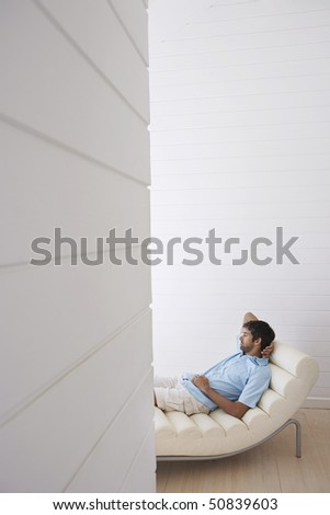 Man lying in reclining chair, half length