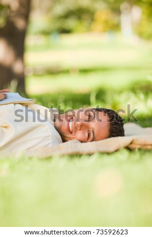Man lying in the park with his book