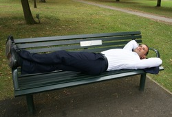 Man lying on a park bench