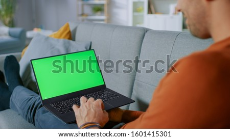 Photo of  Man Lying on His Sofa At Home, Uses Laptop with Green Mock-up Screen. Over The Shoulder Shot of Anonymous Man in the Living Room.