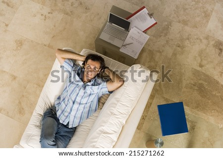 Man lying on sofa beside laptop on coffee table at home, hands behind head, smiling, overhead view