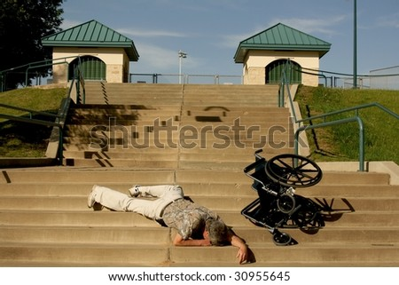 man lying on stairs after wheelchair tips over