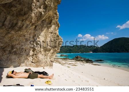 Man lying on the deserted beach in Japan