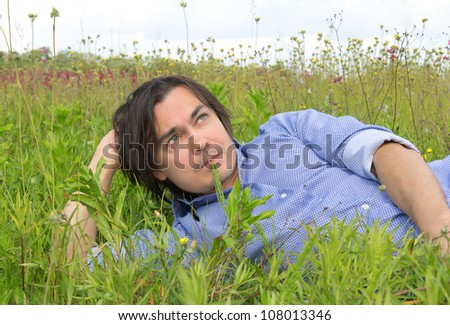 Man lying on the grass with a blade of grass in his mouth