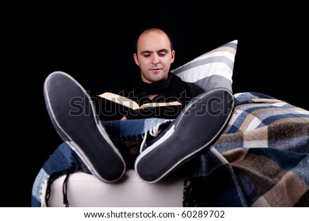 man lying on the sofa reading a book, isolated on black, studio shot.