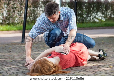 Man lying unconscious girl in recovery position Stock photo ©