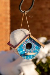 Man-made decorated birdhouse with a show on a roof hanging in front of a family home.