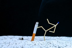 Man made of matches kicking cigarette butt in sand. kicks cigarette. Concept of quiting smoking or tobacco addiction. Stop smoking, quitting smoking concept.