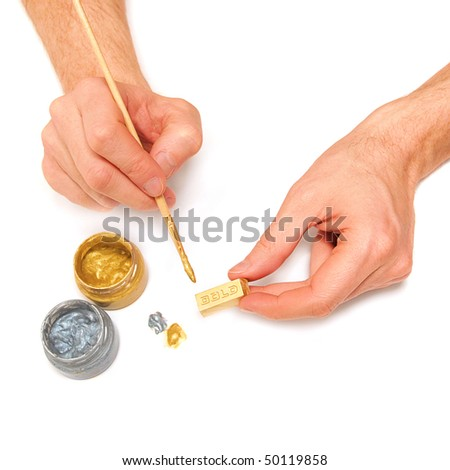 Man makes a gold bar. Bullion, brush, paint and hands isolated on white