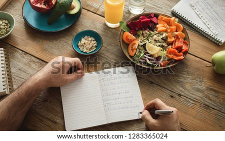Man makes a list of healthy food. Healthy lifestyle diet food concept ストックフォト ©