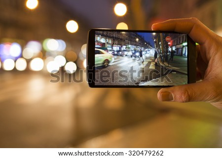 Man makes a picture in the street with his mobile phone. Night light bokeh background