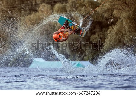 Man makes an extreme jump on wakeboarding, around there are a lot of splashes and splashes of water. This is an extreme sport.