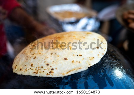 Man making an ulta tawa paratha bread on an upturned pot mughal cuisine from india and pakistan. This flat bread is cooked on an upturned pot covered in oil and ghee and pressed on it by a wet cloth