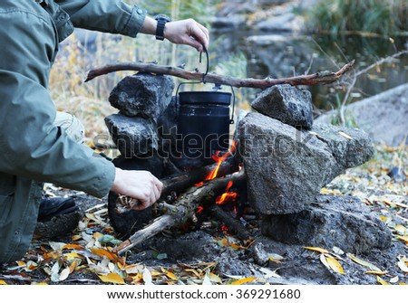 Man making fire in mountains #369291680