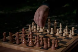 man making first move in a chess game, pawn two steps ahead seen from blacks