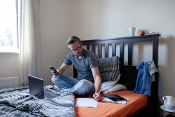 Man making notes whist working from home, sat on bed