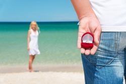 man making proposal with engagement ring and gift box to his woman at sea beach - wedding concept
