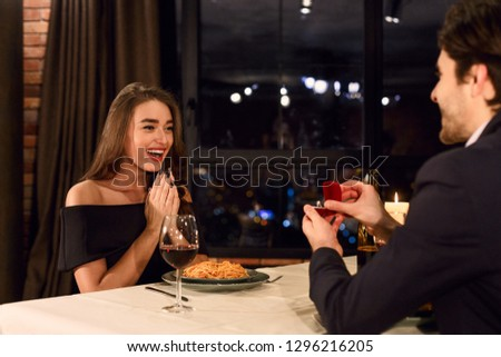 Man making propose with ring to his surprised girlfriend. Surprising proposal concept #1296216205