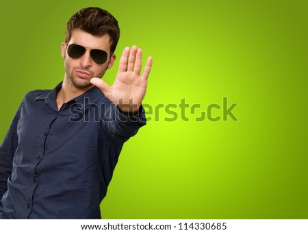 Man Making Stop Sign Isolated On Green Background