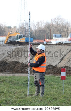 Man making taking measurements in construction site