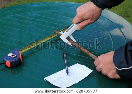 Man measures metal rod diameter with caliper. Nearby is roulette, pen and paper sheet.