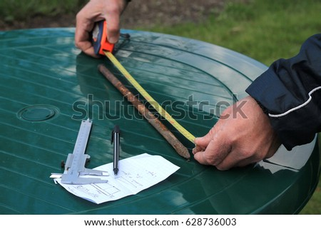 Man measures metal rod length with roulette. Nearby is caliper, pen and paper sheet.