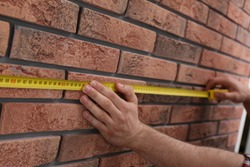 Man measuring brick wall, closeup. Construction tool
