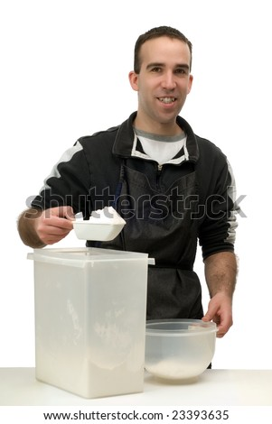 Man measuring some flour for his baking, isolated against a white background
