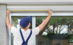 Man measuring window prior to installation of roller shutter outdoors