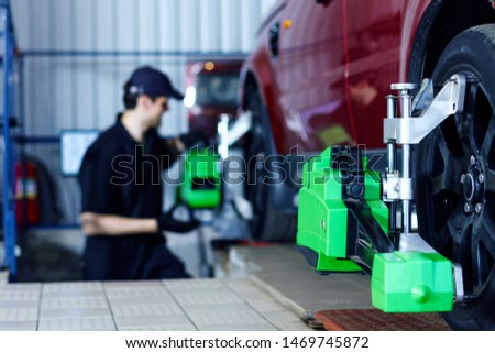 Man mechanic is repairing red car at modern service station. Repairer in blue jumpsuit and cap is adjusting sensors on wheels. Process of wheels alignment camber check in workshop auto repair shop.