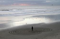 Man meditating in labyrinth maze on beach at sunset