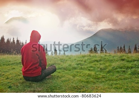 Man meditating in the mountains during the dawn