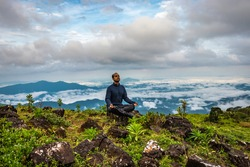 man meditating on rock isolated at the serene nature with amazing cloud layers in background image is showing the breathtaking beauty of nature at south india.