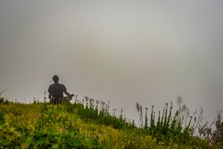 man meditating on rock isolated at the serene nature with white cloud background image is showing the breathtaking beauty of nature at south india.
