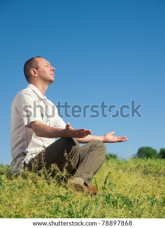 Man meditating on top of hill in park