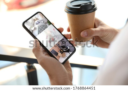 Man monitoring modern CCTV cameras on smartphone indoors, closeup. Home security system Photo stock ©