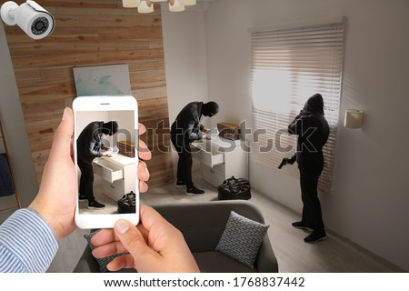 Man monitoring situation at his house with CCTV app on smartphone, closeup. Thieves stealing money  Foto stock ©