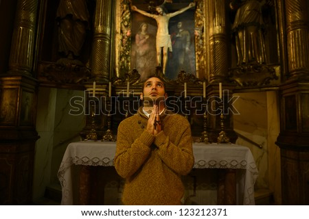 man, monk praying at the altar inside the church