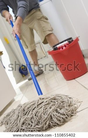 Man Mopping On The Floor