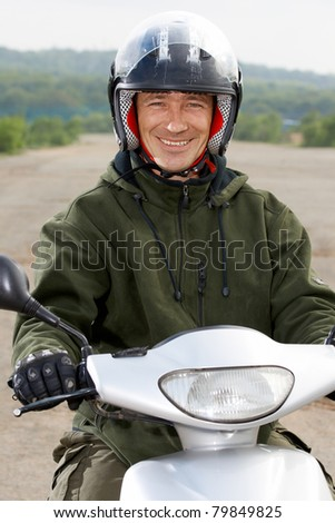 Man motorbiker on the scooter an the outdoor