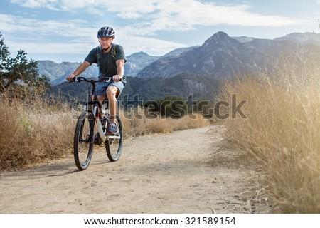 Man mountain biking wearing a water backpack