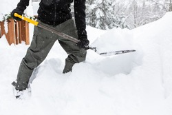 Man moving a shovel full of snow while shoveling snow piles from the backyard during snowfall. Manual snow removal after a heavy snowstorm concept.