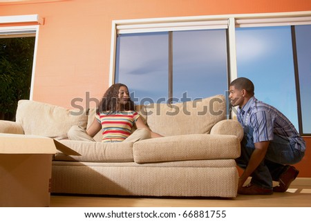 Man moving couch with woman sitting on it