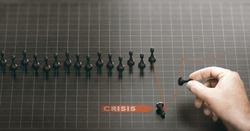 Man moving pawns over a red chart to recover from a crisis. Business continuity plan or disaster recovery concept. Composite image between a hand photography and a 3D background.