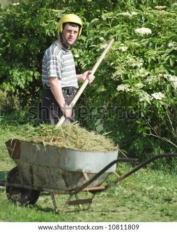 man mowing down grass with scythe