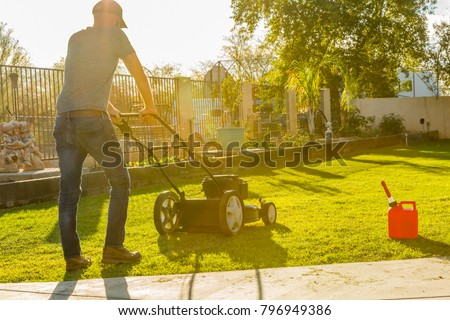 Man mowing lawn with push mower at miday, gas tank near by.  #796949386