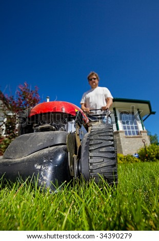 man mowing the front lawn with focus on the front