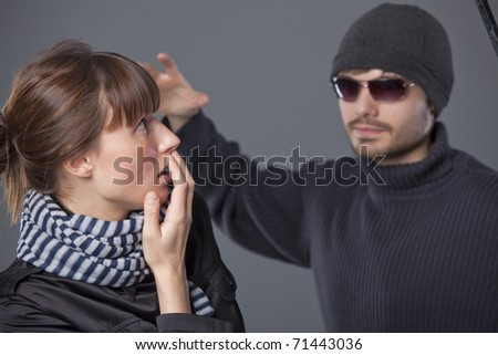 man mugging woman - shot over grey background