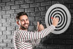 Man near dartboard on dark brick wall